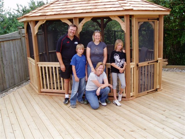 wooden 10 by 14 foot oval gazebo with happy family standing in front